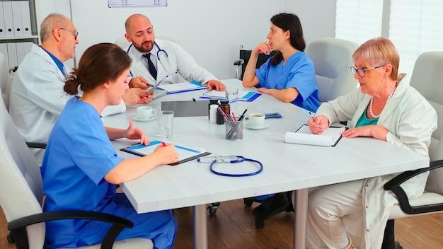 방사선 사진을 분석하는 병원 회의실에서 일하는 의료 전략을 계획하는 건강 솔루션을 찾으려고 노력하는 의사 팀. 질병에 대해 이야기하는 클리닉 치료사, 의학 전문가