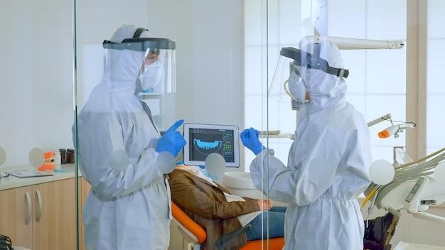 タブレット計画治療を使用して歯のデジタルx線を分析する患者の近くに立っている完全なウイルス対策の制服を着た医師のチーム。コロナウイルスの発生における新しい通常の歯科医の訪問の概念。