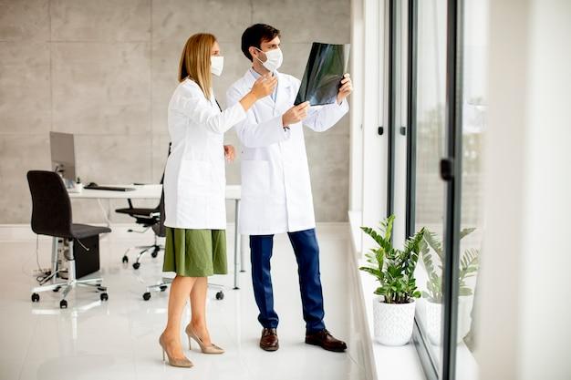 Команда врачей с защитными масками для лица изучает рентгеновский снимок в офисе