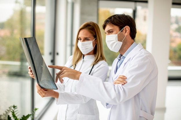 사무실에서 xray를 검사하는 보호용 얼굴 마스크가있는 의사 팀