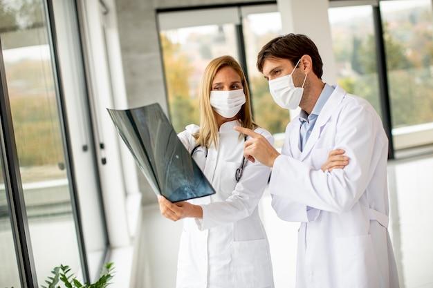 사무실에서 xray를 검사하는 보호 얼굴 마스크가있는 의사 팀