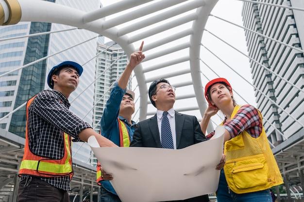 青写真会議を開催し、都市の建設現場での新しいプロジェクトについて話し合うビジネスマンとエンジニアのチーム