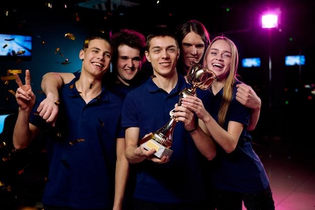 Команда возбужденных подростков-участников соревнований по компьютерным играм показывает приз за победу