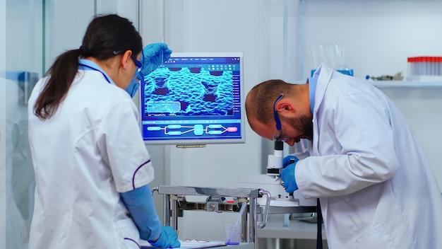 近代的な設備の整った実験室で顕微鏡に取り組んでいる経験豊富な生物学者のチーム。科学者たちは、covid19ウイルスに対するハイテク研究診断を使用してワクチンの進化を調べています