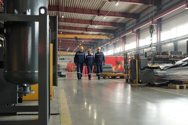 압축기 공장 작업장을 가로질러 새로운 장비에 대해 논의하는 안전모 공장 노동자 팀