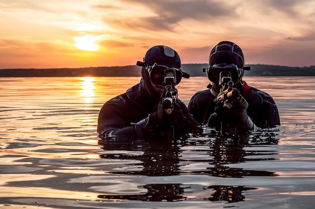 Бригада бойцов спецподразделения движется по воде для выполнения задания. понятие нестабильности, военные действия, холодная война. смешанная техника
