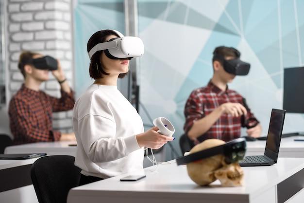 Команда из четырех креативных инженеров, работающих с виртуальной реальностью, молодая женщина тестирует очки виртуальной реальности или очки, сидя в офисном помещении