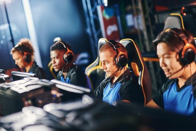 E스포츠 토너먼트에 참가하는 헤드폰을 착용한 4명의 전문 사이버스포츠 게이머 팀