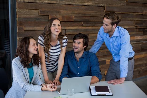 Команда графических дизайнеров, улыбаясь при использовании ноутбука