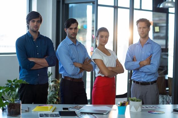 Команда графических дизайнеров, стоящих со скрещенными руками
