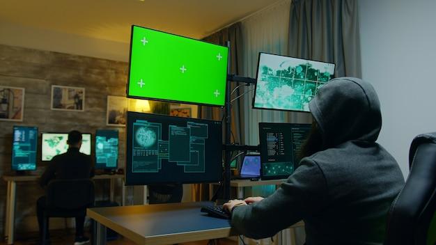 사이버 범죄에 위험한 바이러스를 만드는 해커 팀. 녹색 화면이 있는 컴퓨터.