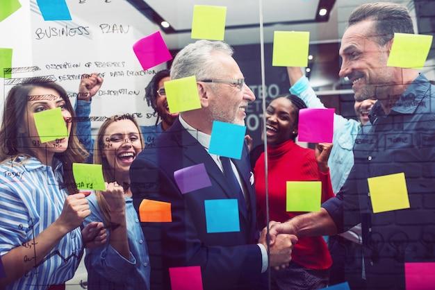 幸せな人々のチームは、オフィスで一緒に働きます。チームワーク、パートナーシップ、成功の概念