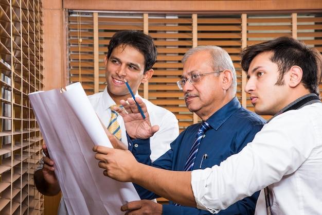 인도 건축가 또는 건축업자 팀이 건물 모델로 주택 프로젝트의 초안을 작성하거나 논의하고 회의 테이블 선택적 초점을 중심으로 계획