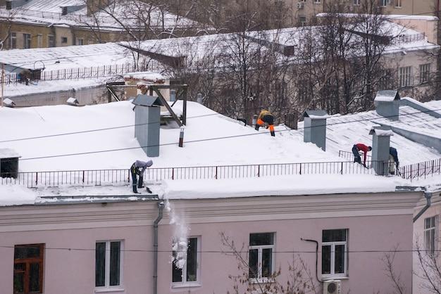 男性労働者のチームは、マントラのベルトを固定する際にシャベルで雪から建物の屋根を掃除します。