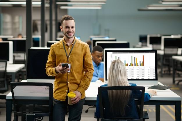 Команда менеджеров на своих рабочих местах в ит-офисе. профессиональная командная работа и планирование, групповой мозговой штурм и корпоративная работа, современный интерьер компании на заднем плане