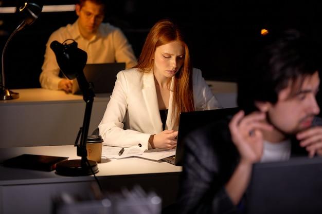 컴퓨터를 사용하여 매우 늦게 프로젝트에 참여하는 관리자 사무실 직원 팀. 정장을 입은 열심히 일하는 사람들은 일, 생각, 브레인스토밍, 스마트폰으로 빨간 머리 여성에 초점을 맞춥니다.