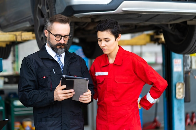 Бригада механиков обсуждает в ремонтном гараже. бригада профессиональных специалистов по ремонту автомобилей.