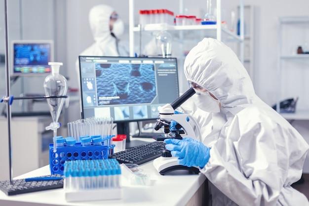 現代の実験室でコロナウイルス分析を行う医療用個人用ppeスーツのチーム。生化学実験室でのcovid-19チェックサンプルによる世界的大流行中の化学者研究者
