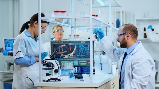 현미경, 시험관, 마이크로피펫을 사용하여 백신 개발을 수행하고 현대적인 시설을 갖춘 실험실에서 클립보드에 분석 결과를 기록하는 의학 연구 과학자 팀