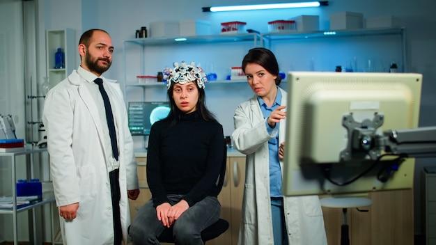 Группа медицинских исследователей, исследующих нервную систему пациентки, вместе смотрит на сканирование мозга на мониторе компьютера