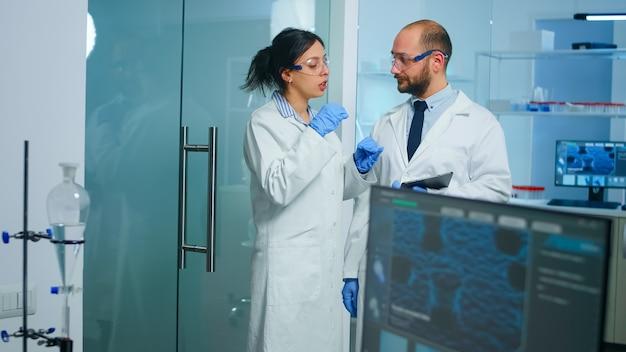 첨단 기술의 도움으로 백신 개발을 수행하는 의료 과학자 팀, 새로운 정보를 분석하는 태블릿을 들고있는 의사