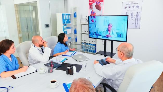 Команда медицинского персонала во время видеоконференции с врачом в конференц-зале больницы. медицинский персонал использует интернет во время онлайн-встречи с опытным врачом для экспертизы, медсестра делает заметки.