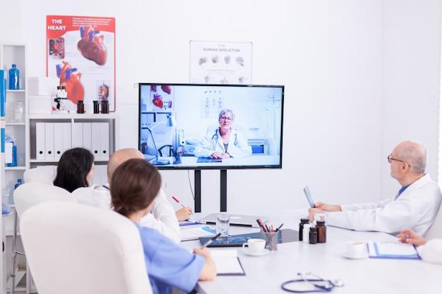 병원 회의실에서 의사와 화상 회의를 하는 동안 의료진 팀. 전문 의사와 온라인 회의 중 인터넷을 사용하는 의료 직원.