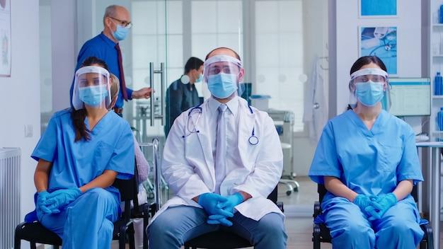 Команда медицинского персонала с защитной маской и козырьком от коронавируса в зоне ожидания больницы смотрит в камеру. пациент в кабинете для консультации.