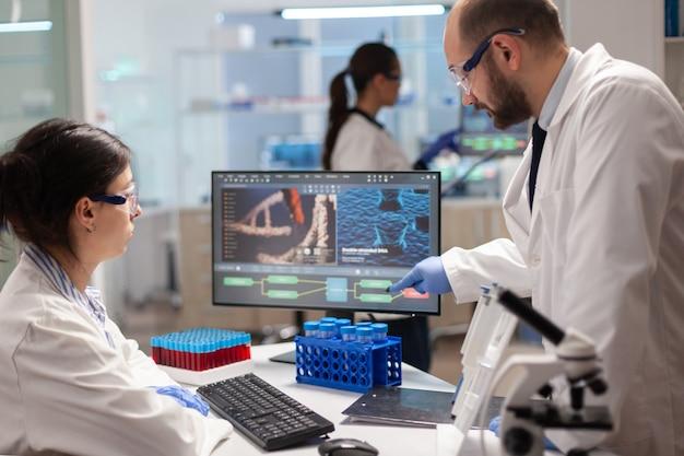 현대식 시설을 갖춘 실험실에서 백신 개발에 대해 논의하는 미생물 과학자 팀