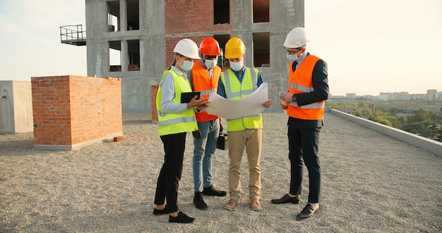 Бригада мужчин и женщин-конструкторов смешанной расы в шлемах и медицинских масках стоит на вершине здания и обсуждает проект плана строительства. концепция пандемии. инженеры и архитекторы.