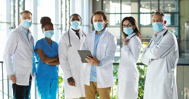 病院のプロの男性と女性の医師の混血のチーム。タブレットデバイスを備えた医療用マスクの国際的な医療グループ。クリニックのガウンとユニフォームを着た多民族の医師。