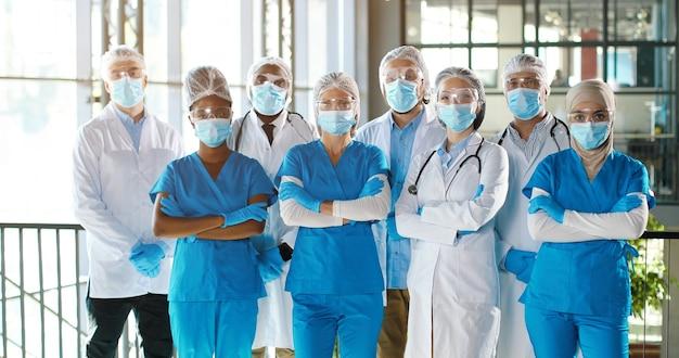 病院のプロの男性と女性の医師の混血チームのチーム。屋内。医療用マスクの国際的な衛生兵グループ。クリニックでガウンとユニフォームを着た多民族の医師。
