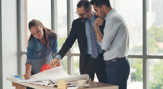 Команда многоэтнических архитекторов работает над планами строительства в конференц-зале. инженеры обсуждают проект в офисе. зрелые бизнесмен и женщина, стоя вокруг стола, работая над светокопией.