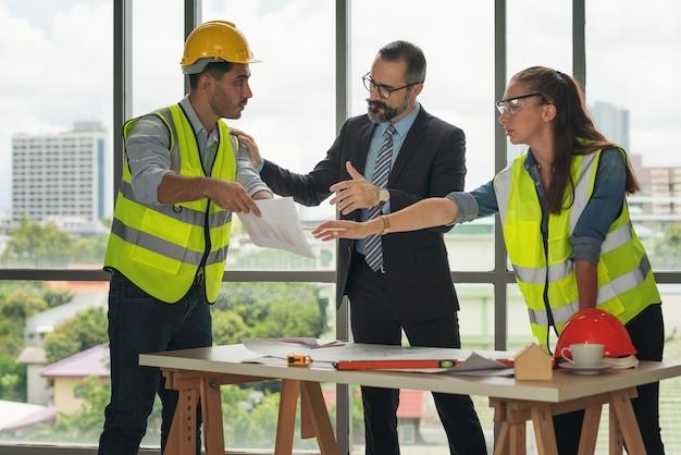 회의실에서 건설 계획에 종사하는 다민족 건축가의 팀. 사무실에서 프로젝트에 대해 논의하는 엔지니어. 성숙한 사업가 청사진에 작업 테이블 주위에 서있는 여자.
