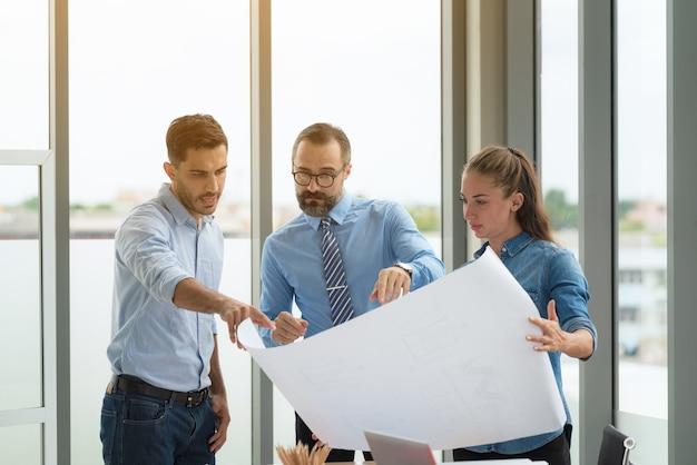 회의실에서 건설 계획에 종사하는 다민족 건축가의 팀. 사무실에서 프로젝트에 대해 논의하는 엔지니어.