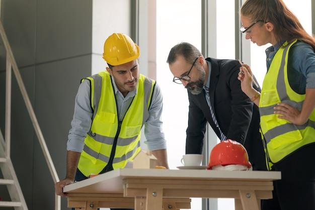 会議室で建設計画に取り組んでいる多民族建築家のチーム