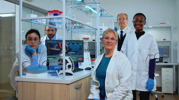 近代的な設備の整った実験室でカメラを見ている実験室に座っている多民族の科学者のチーム。科学研究、ワクチン開発のためにハイテクを使用してウイルスの進化を調べる医師のグループ。