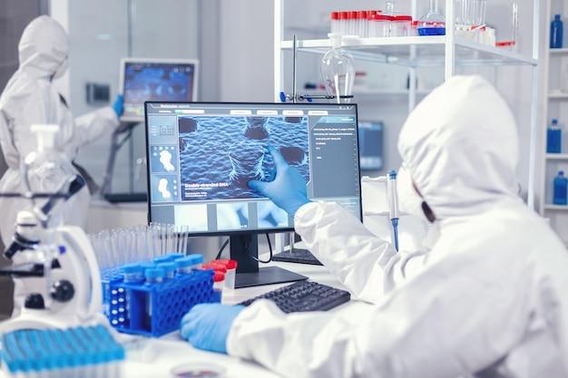 Команда исследователей-фармацевтов, работающих в современной лаборатории, одета в защитный костюм. инженеры лаборатории проводят эксперимент по разработке вакцины против вируса covid19
