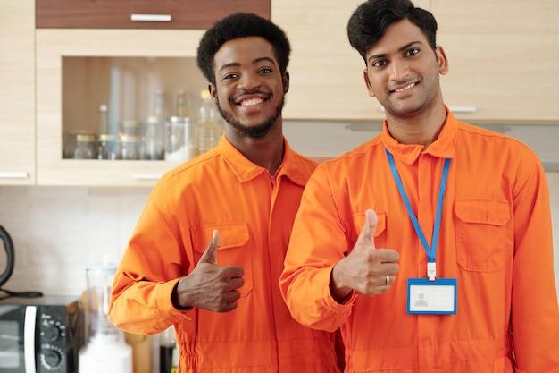 작업복을 입은 긍정적인 배관공 팀이 부엌에 서 있을 때 웃고 엄지손가락을 치켜들고 있습니다.