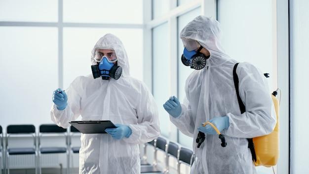 行われた作業の記録を作成するプロの男性消毒剤のチーム。健康保護の概念。