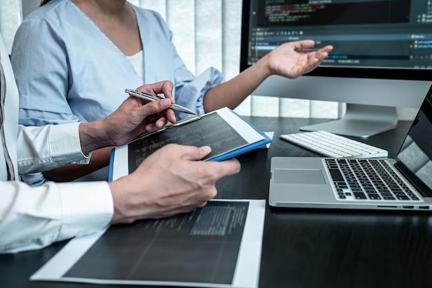 Команда программистов, работающих над программным обеспечением на компьютере с javascript в ит-офисе, пишет коды и веб-сайты с кодами данных и кодирует технологии баз данных, чтобы найти решение проблемы.