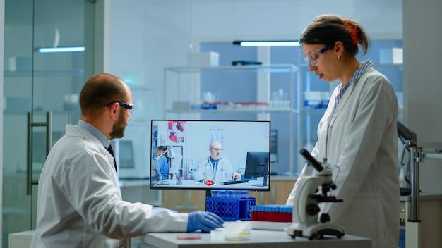 Команда ученых консультируется с профессиональным врачом по видеосвязи, обсуждает во время виртуальной встречи в медицинской лаборатории. химик изучает эволюцию вакцины с использованием высокотехнологичных исследований лечения