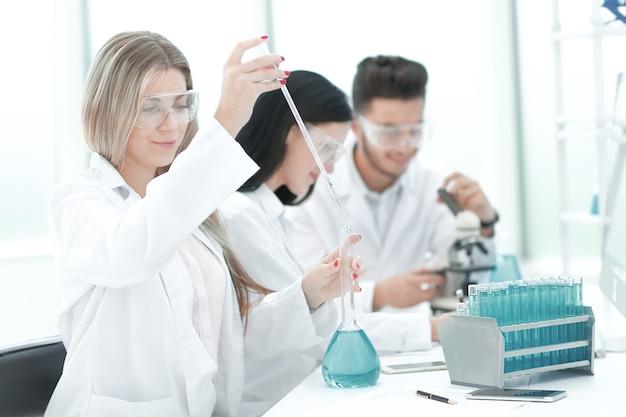 科学者のチームは、実験室で流体研究を実施します。