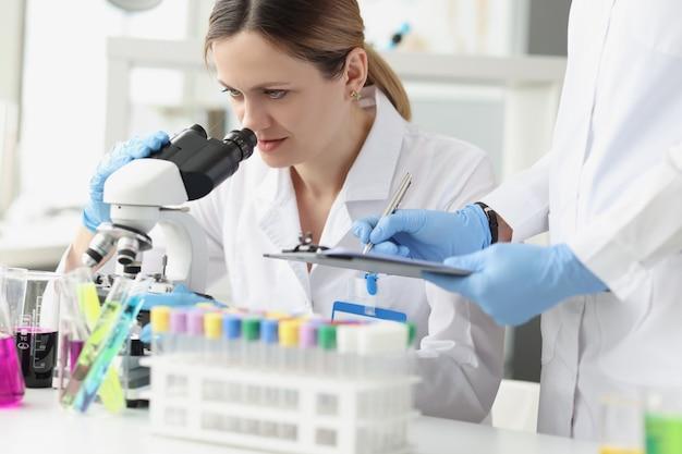 Команда ученых проводит лабораторные исследования с помощью микроскопа. концепция современных методов микроскопии