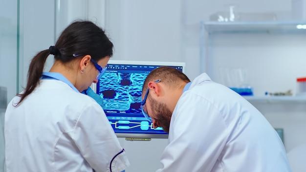 近代的な設備の整った実験室でpcの前でウイルスの発生について議論している科学者のチーム。治療を研究するためのハイテクを使用してワクチンの進化を分析する多民族のもの