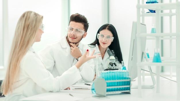 책상에서 뭔가를 논의하는 과학자 팀.