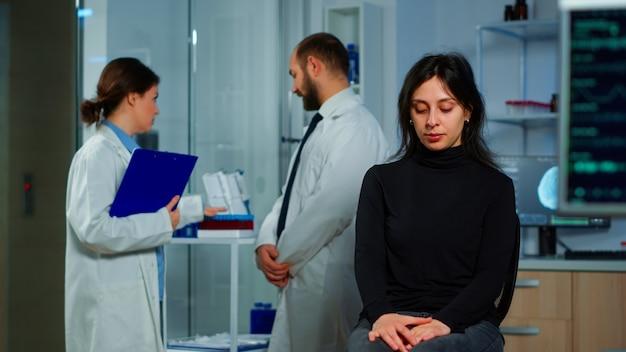 Команда ученых-врачей обсуждает состояние здоровья пациента, функции мозга, нервную систему, томографическое сканирование, пока женщина ждет диагноза заболевания, сидя в неврологической исследовательской лаборатории