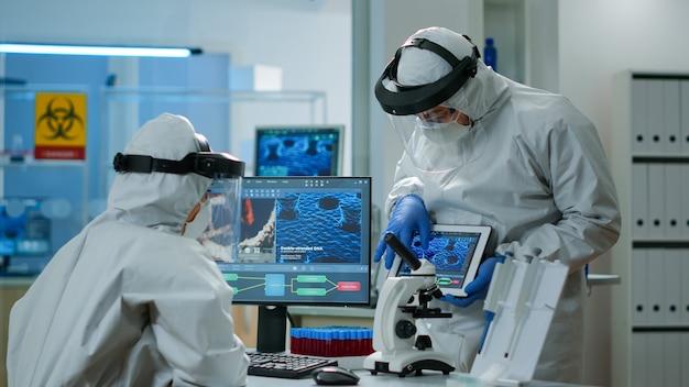 設備の整った実験室でpcとタブレットの前でウイルスの発生について話し合っている科学者のチーム。治療を研究するためのハイテクを使用してワクチンの進化を分析する医療関係者