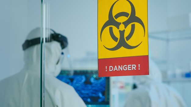 화학 실험실의 위험 구역에서 일하는 바이러스 돌연변이를 연구하는 작업복을 입은 과학자 팀. covid19에 대한 진단을 위해 첨단 기술을 사용하여 백신 진화를 검사하는 의사 그룹