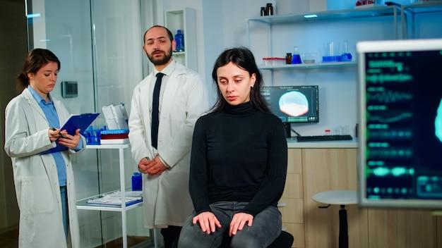 Команда ученых, специализирующихся на неврологической медицине, обсуждает состояние здоровья пациента, функции мозга, нервную систему, томографическое сканирование, пока женщина ждет диагноза болезни, сидя в лаборатории